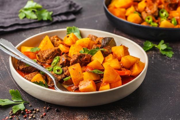 Rundvlees dat met aardappels in tomatensaus wordt gestoofd, donkere achtergrond.