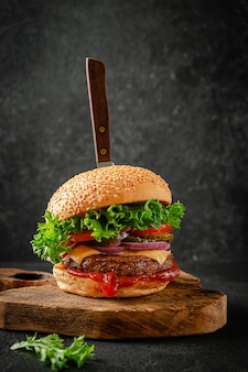 Rundvlees hamburger met mes op een houten bord. amerikaans straatvoedselconcept.