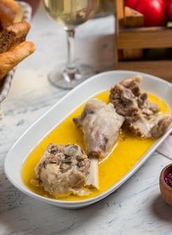 Rundvlees, lamsstukjes gebakken in bouillon botersaus en geserveerd met sumakh.