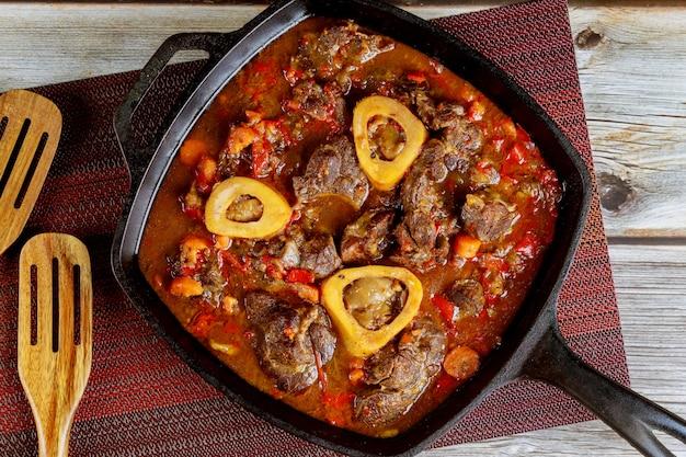 Rundvlees met bot gestoofd in ijzeren koekenpan met wortel, ui en rode paprika.
