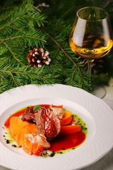 Rundvlees met kaki en glas witte wijn op kerstboom. vlees gevuld met fruit.