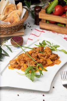 Rundvlees plakjes stoofvlees in tomatensaus met uien en paprika. geserveerd in witte plaat met basilicum.