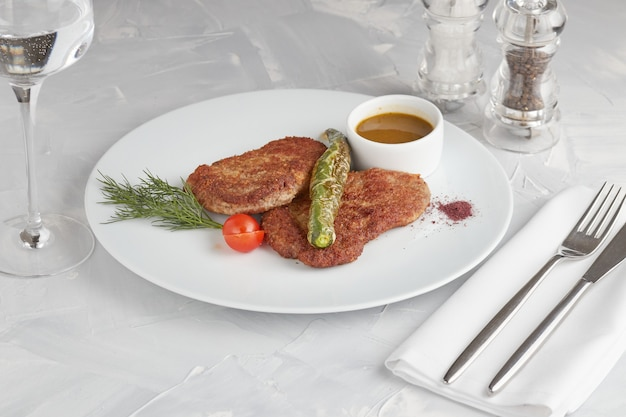 Rundvlees schnitzel op een witte plaat, lichte achtergrond Premium Foto