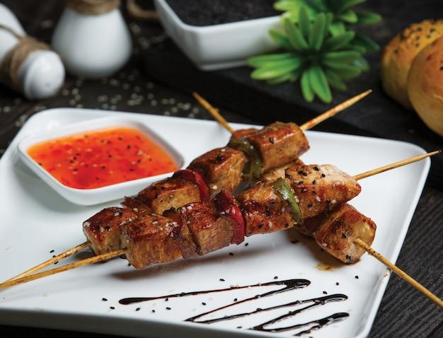 Rundvlees shish kebab met hete chilisaus.