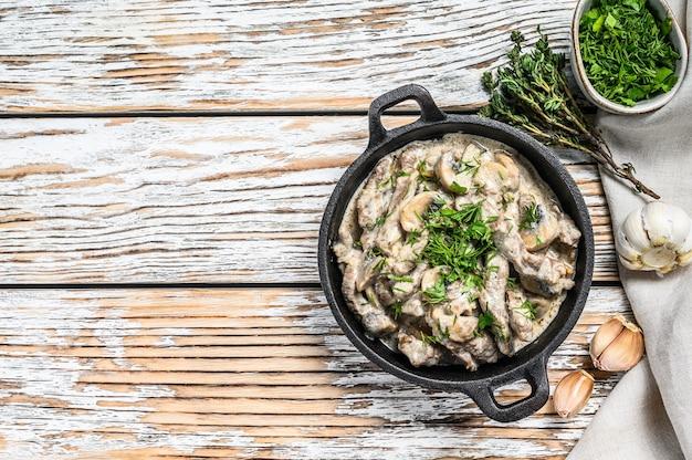 Rundvlees stroganoff met champignons in koekenpan. witte achtergrond. bovenaanzicht. kopieer ruimte.