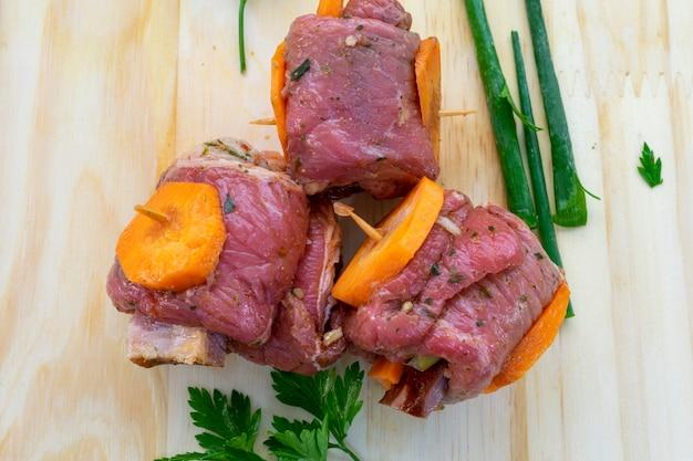 Rundvleesbroodje met wortel en bacon, brachola of braciola genoemd. klaar om te koken. bovenaanzicht