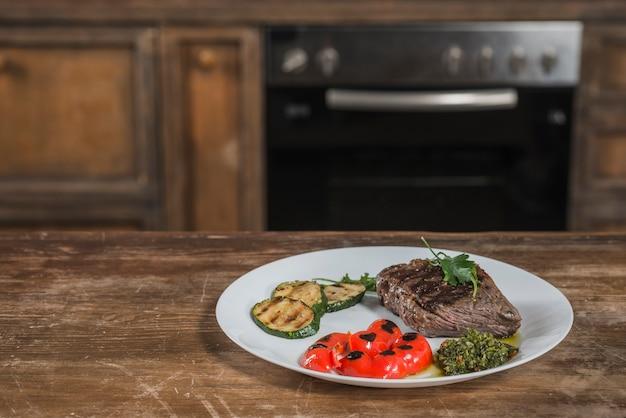 Rundvleesfilet met geroosterde tomatenkers en komkommer op witte plaat
