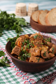 Rundvleesgoulash bevindt zich in een bruine kom op tafel