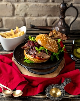 Rundvleeshamburger in sesambroodje dat met gebraden gerechten wordt gediend