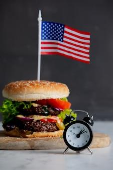 Rundvleeshamburger met de vlag van de vs op dienblad en wekker