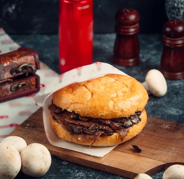 Rundvleeshamburger met paddestoel die in document zak wordt verpakt die op scherpe raad wordt gediend