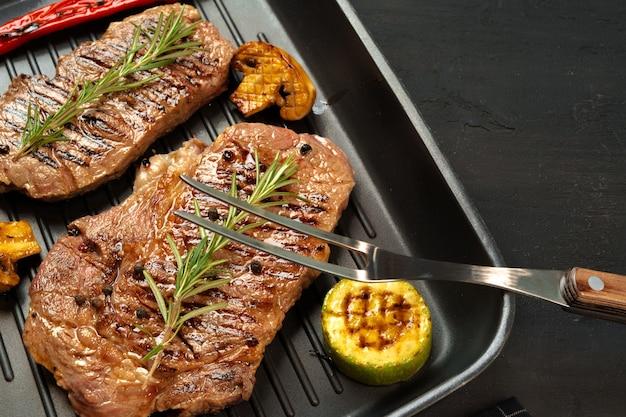 Rundvleeslapjes vlees met groenten op grillpan, hoogste mening