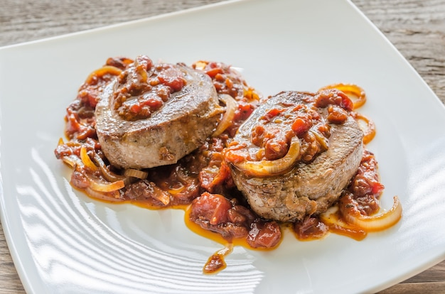 Rundvleeslapjes vlees met tomatensaus op een witte plaat