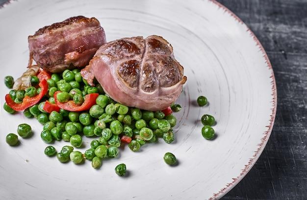 Rundvleesmedaillons omwikkeld met spek, serveren met groene erwten en op een bord op houten achtergrond.