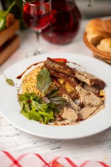 Rundvleesrek in crème botersaus geserveerd met rijst garnituur en groene salade.