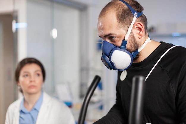 Runner atleet cardio hartslag testen in sport uithoudingsvermogen laboratorium met masker en elektroden op lichaam, vo2. sportman training met sensor op kruisonderzoek.