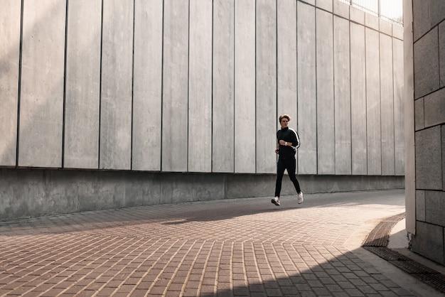 Runner atleet loopt in de buurt van het stadion. man joggen training wellness-concept.