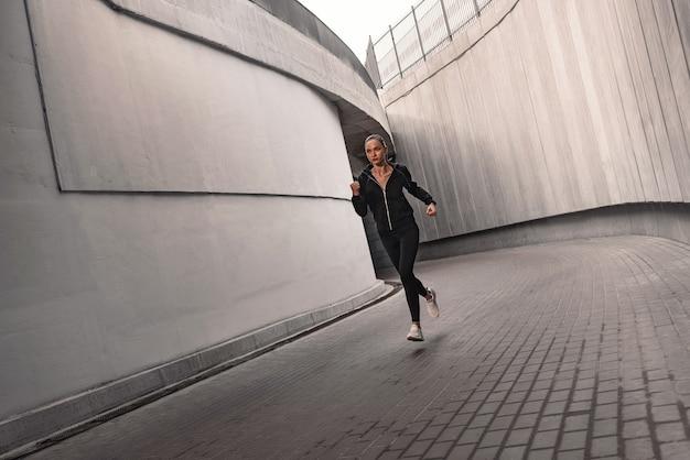 Runner atleet loopt in de buurt van het stadion. vrouw joggen training wellness-concept.