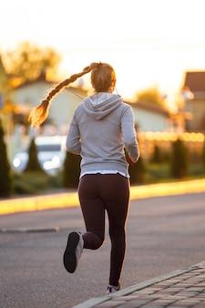 Runner atleet uitgevoerd op weg. vrouw fitness joggen training wellness-concept.
