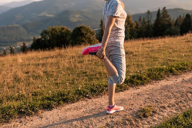 Runner atleet vrouwelijke vrouw voeten lopen op bergweg onder zonlicht.