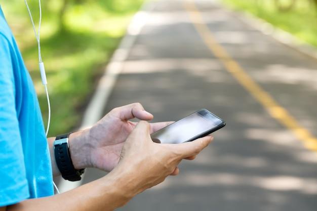 Runner in het park met behulp van smartphone op een weg