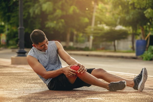 Runner man met sport lopende knieblessure handen met knie met pijnlijke enkelknie twist