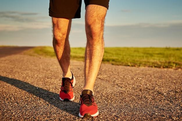 Runner man voeten op de weg bij de zonsondergang