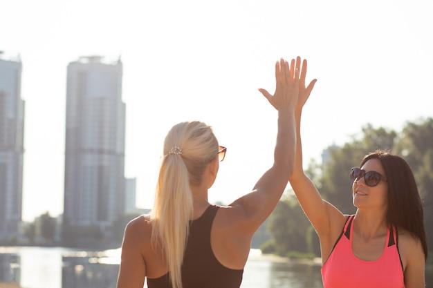 Runner meisjes geven high five in het park. buiten geschoten met zonnestralen. ruimte voor tekst