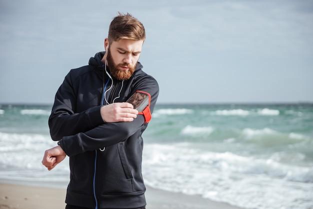 Runner met telefoon in de buurt van de zee kijkend naar telefoon