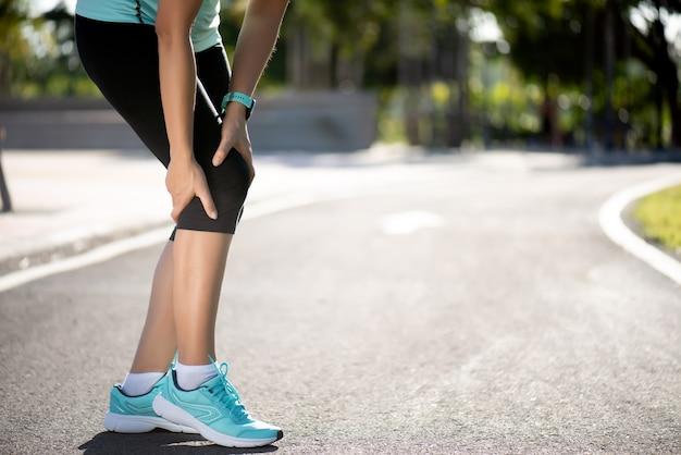 Runner sport knieblessure. de vrouw in kniepijn terwijl het lopen werkt in park uit