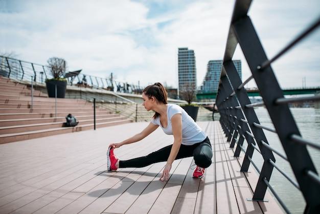 Runner uitrekkende benen vóór fitness training aan de rivier. zijaanzicht.