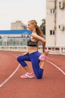 Runner vrouw die zich uitstrekt voor de training