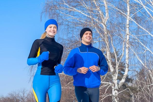 Runners. jonge lopende paren. sport man & vrouw joggen op winter park