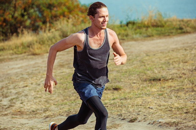 Running sport. man runner sprinten buiten in de schilderachtige natuur. fit gespierde mannelijke atleet training parcours uitgevoerd voor marathon run.