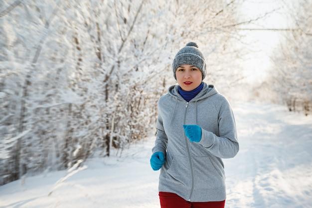 Running sport vrouw. vrouwelijke loper joggen in koude winter woud dragen warme sportieve hardloopkleding en handschoenen.