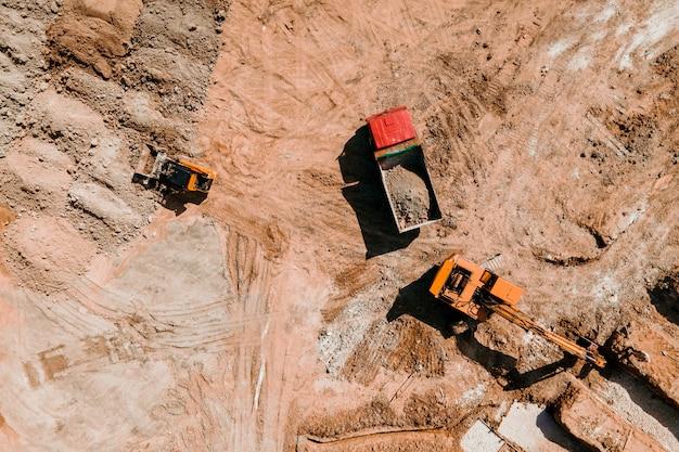 Rupsgraafmachine aan het werk op de bouwplaats top luchtfoto van een rupsbulldozer rijdt op s...