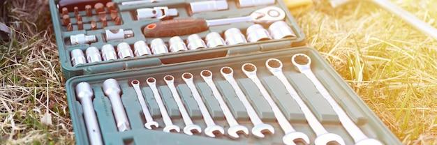 Rusland april 2020. set van verschillende reparatiehandgereedschappen of gereedschappen van automonteurs. reparatie toolkit in een doos op het gras buitenshuis. apparatuur voor de bouw. banner. gloed