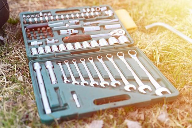 Rusland april 2020. set van verschillende reparatiehandgereedschappen of gereedschappen van automonteurs. reparatie toolkit in een doos op het gras buitenshuis. apparatuur voor de bouw