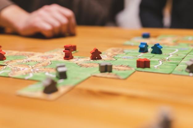 Rusland, december 2020: twee mannenvrienden hebben plezier in het spelen van het bordspel van carcassonne, laat in de avond of 's avonds. mannelijke handen en spelkaarten en chips op tafel