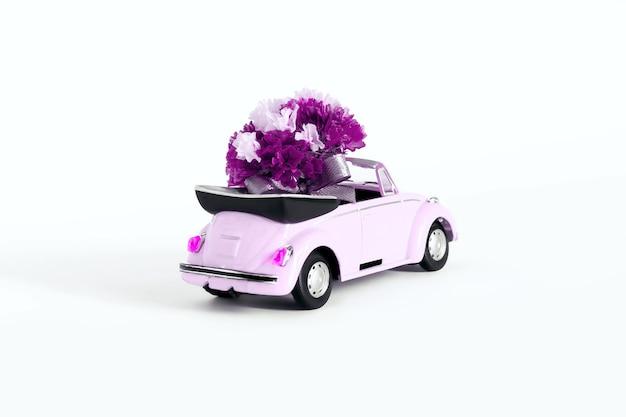 Rusland. moskou. 07.02.2021 roze auto met een boeket bloemen op een witte achtergrond. vakantieconcept, vervoer.
