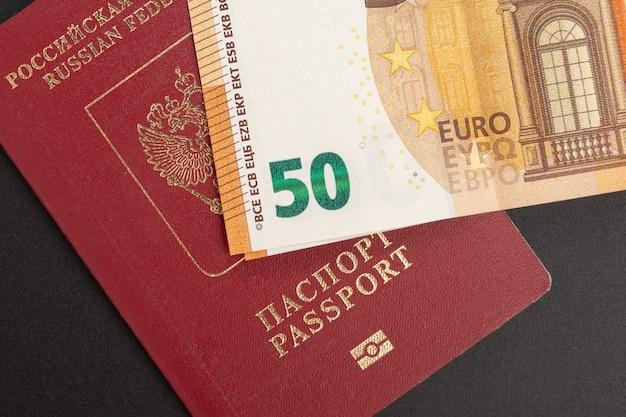 Russisch buitenlands internationaal paspoort en euro op een zwarte achtergrond