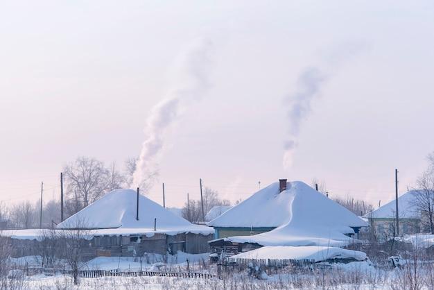 Russisch dorp met oude houten traditionele russische stijl. daken vallende sneeuw tijdens ijzige winterdag.