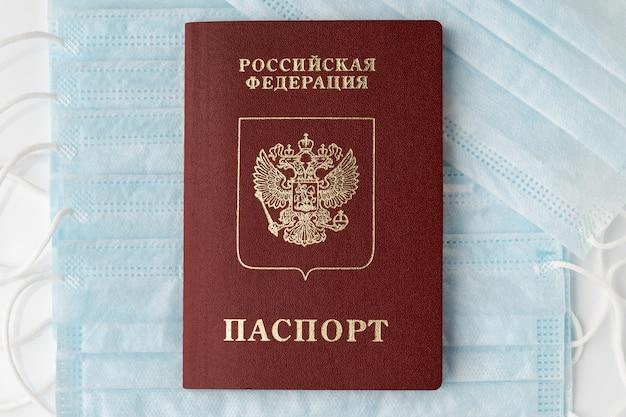 Russisch paspoort op achtergrond van medische gezichtsmaskers. tekst van titeldocument in de russische taal. concept van strijd tegen coronavirus, pandemische verzekering, door de lucht overgedragen ziekten, sars, griep.
