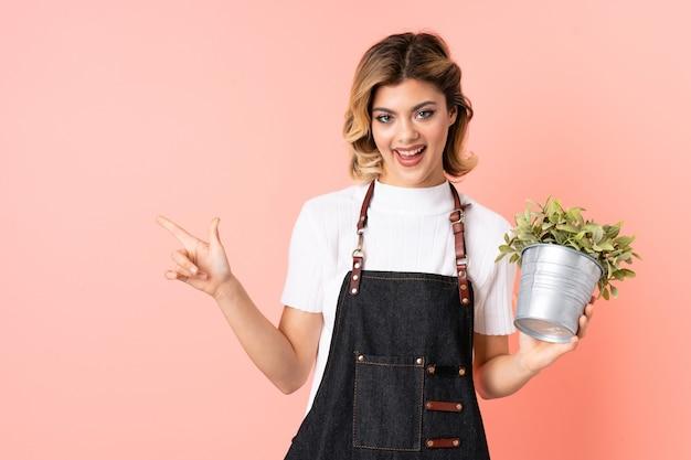 Russisch tuinman meisje met een plant geïsoleerd op roze verrast en wijzende vinger naar de zijkant
