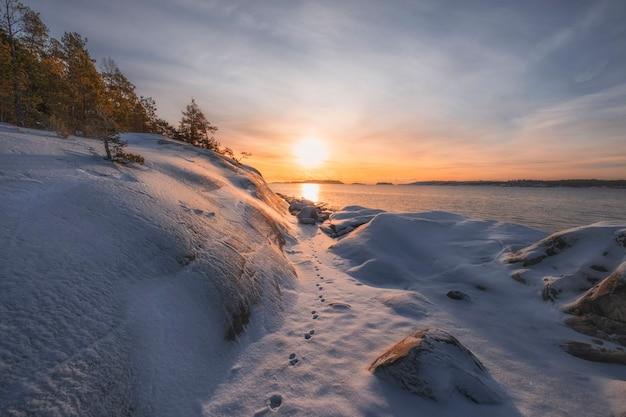Russisch winterlandschap. rotsen en zonsopgang op het meer ladoga eiland kajosaari republiek karelië