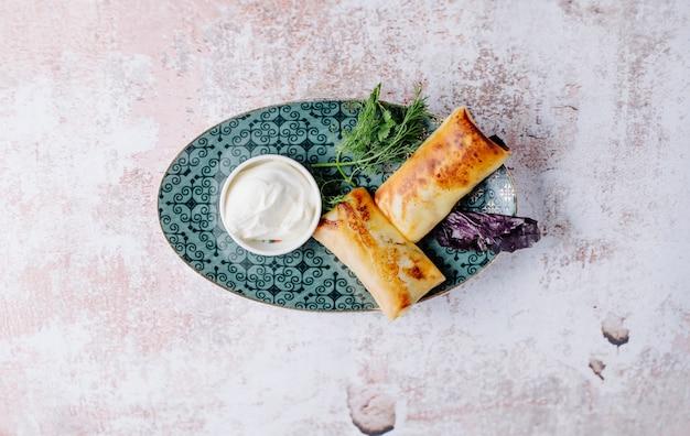 Russische apetizer blinchik in pannenkoeken met kruiden en yoghurt.
