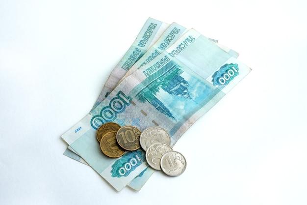 Russische bankbiljetten en munten op een witte ruimte, lay-out voor de werkruimte