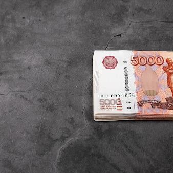 Russische contante bankbiljetten van vijfduizend roebel, de bundel hangt op een grijze achtergrond