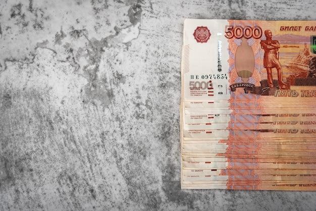 Russische contante bankbiljetten van vijfduizend roebel, de bundel hangt op een grijze achtergrond,