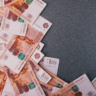 Russische contante bankbiljetten van vijfduizend roebel, verspreid over een grijze ruimte, er is een plaats voor de inscriptie en tekst